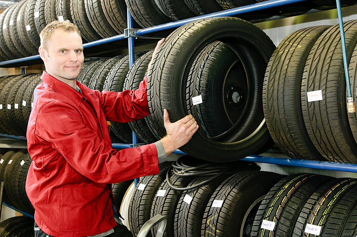 Car mechanic fitting new tyres at garage in Mayfield, Midlothian